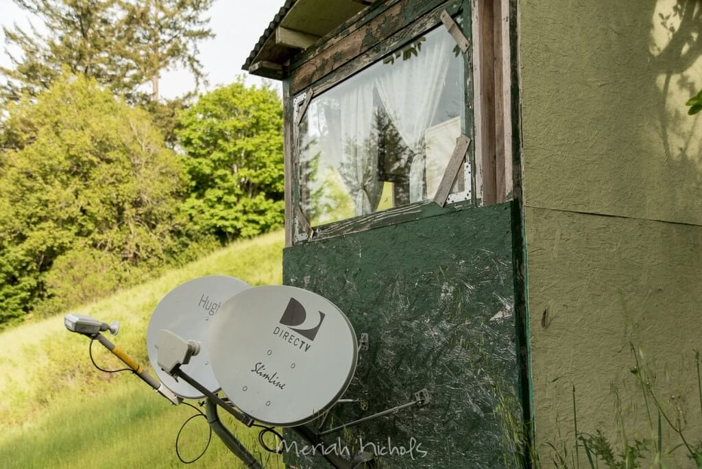 2 satellite dishes are mounted to the outhouse