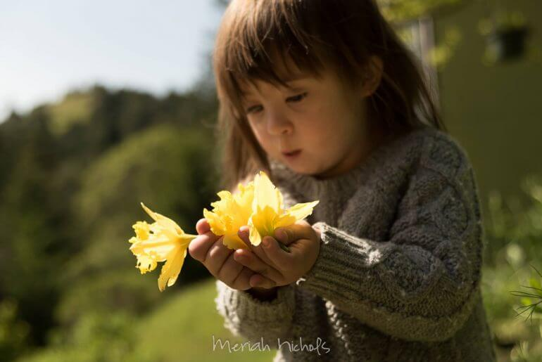 child with Down syndrome looks at yellow daffodils in her hands