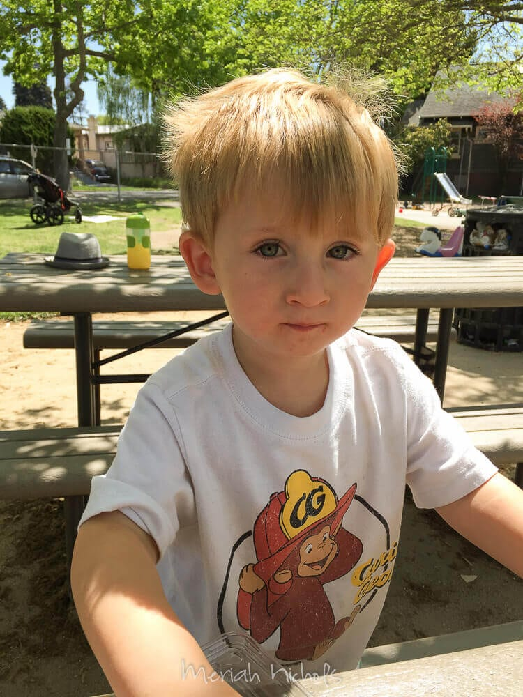 small boy - Mack - (wearing a curious george shirt) looks at the camera