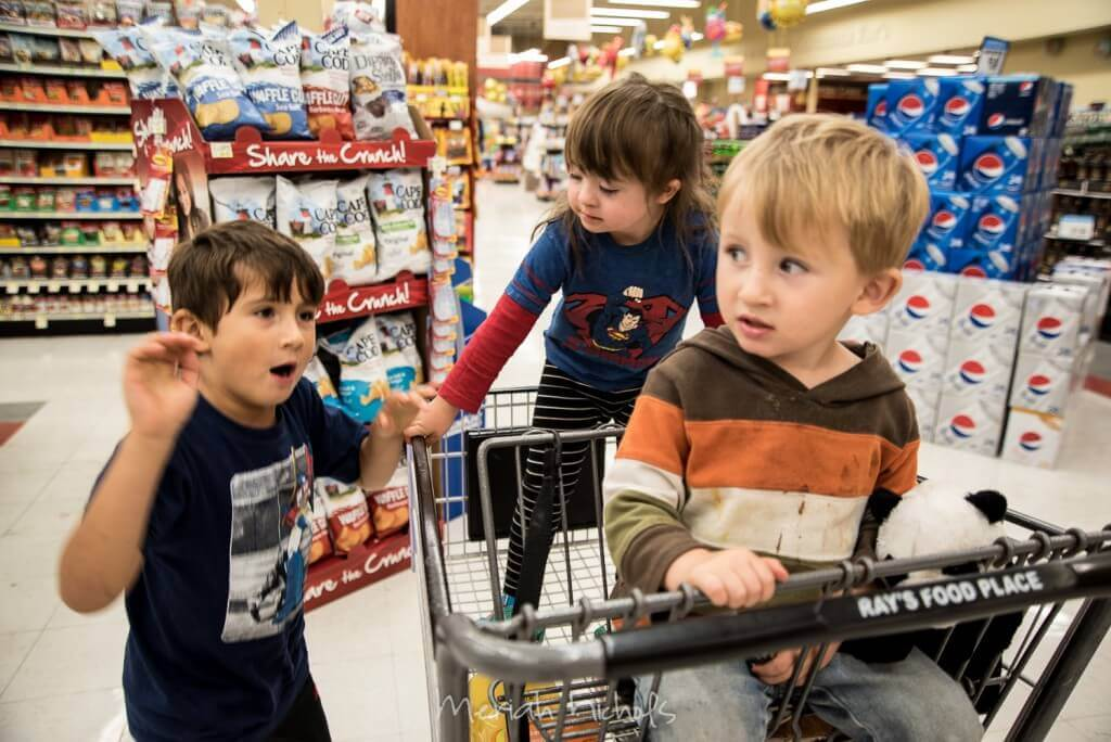 All 3 kids in the supermarket, two of them in a cart and the third (Micah) alongside them
