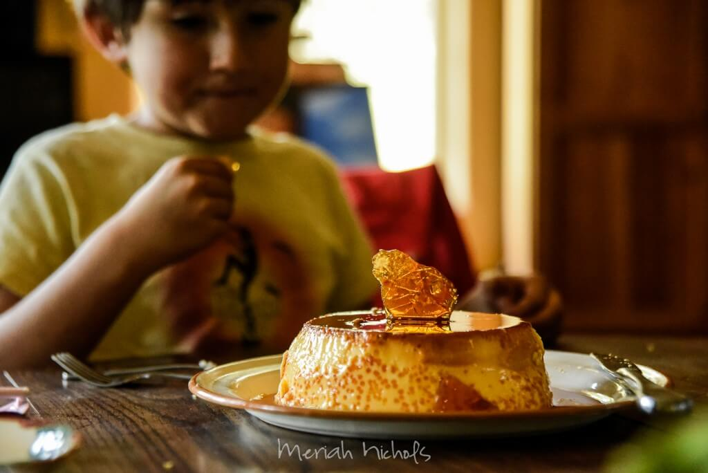 little boy with a flan cake in front of him. he eyes the sugar