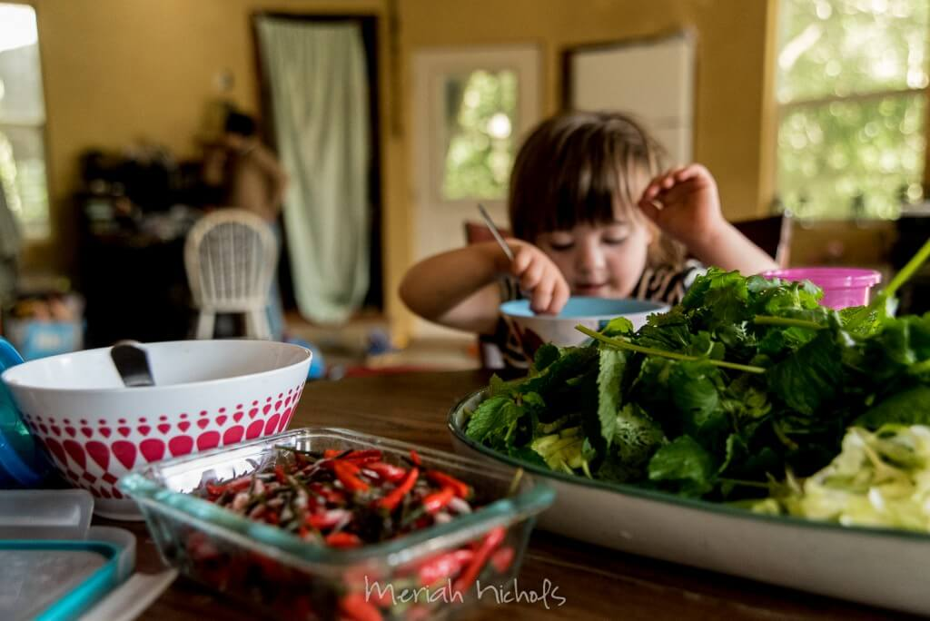 small girl at the far end of the table, with chopped cilantro and chillies in front