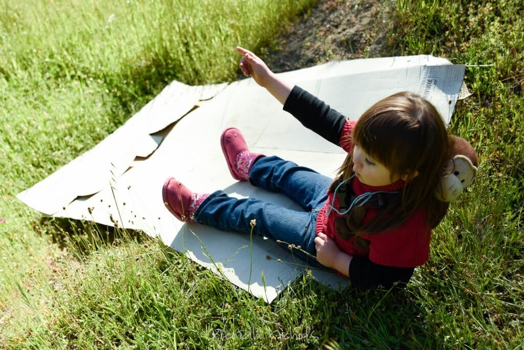 child about to slide down a mound on a piece of cardboard