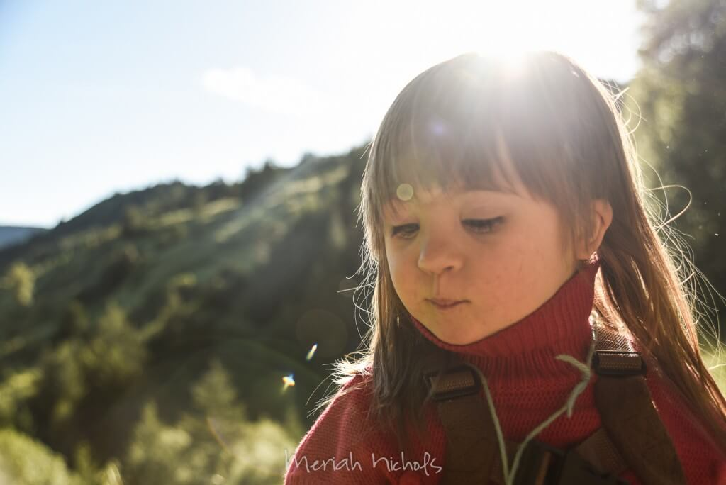 child looking down with light all around her