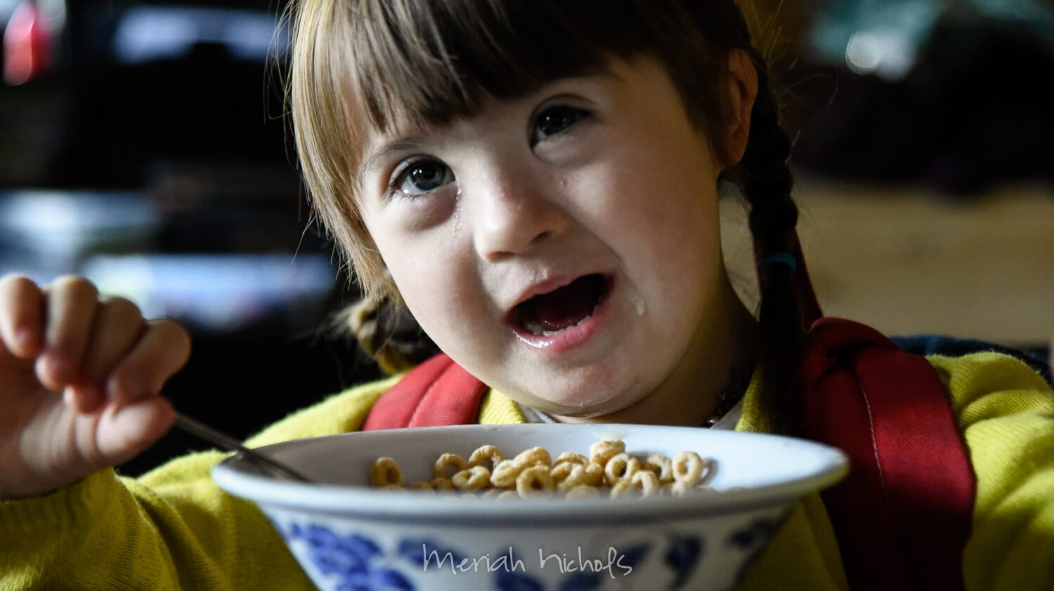 little girl smiles over her cereal