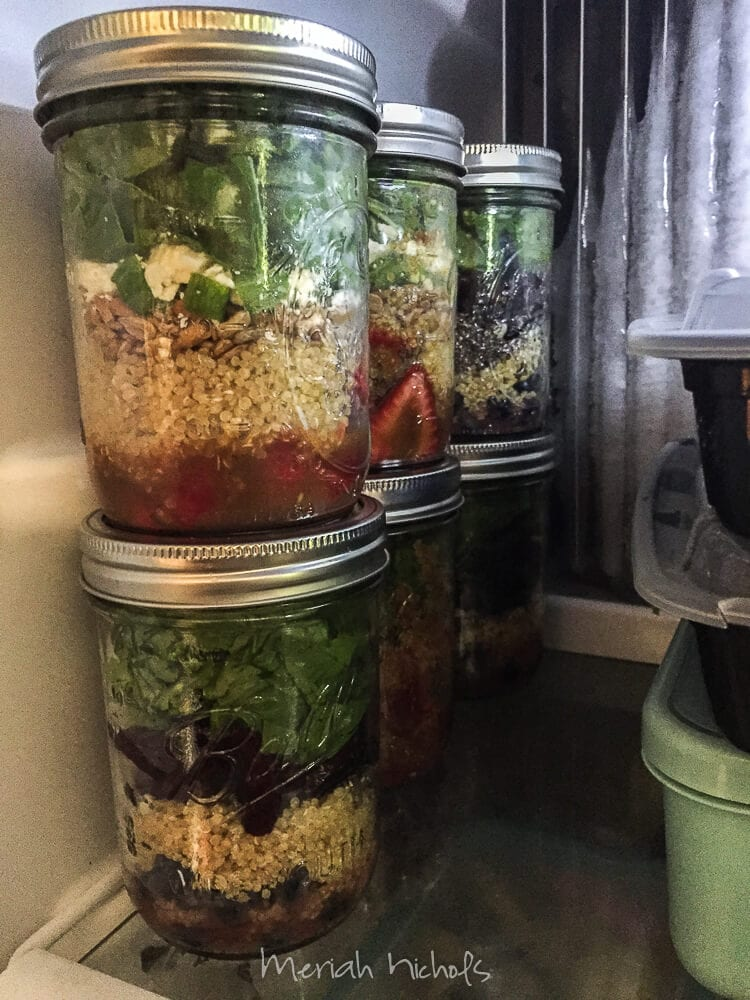 jars filled with food line the shelf in a fridge