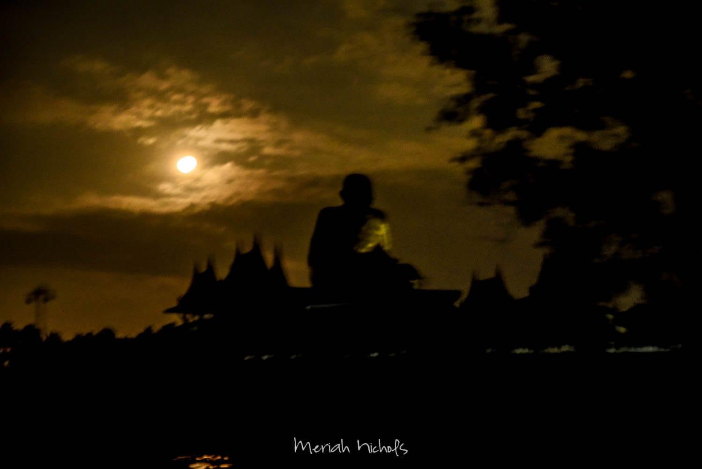 passing by a large statue of Buddha at night by Amphawa