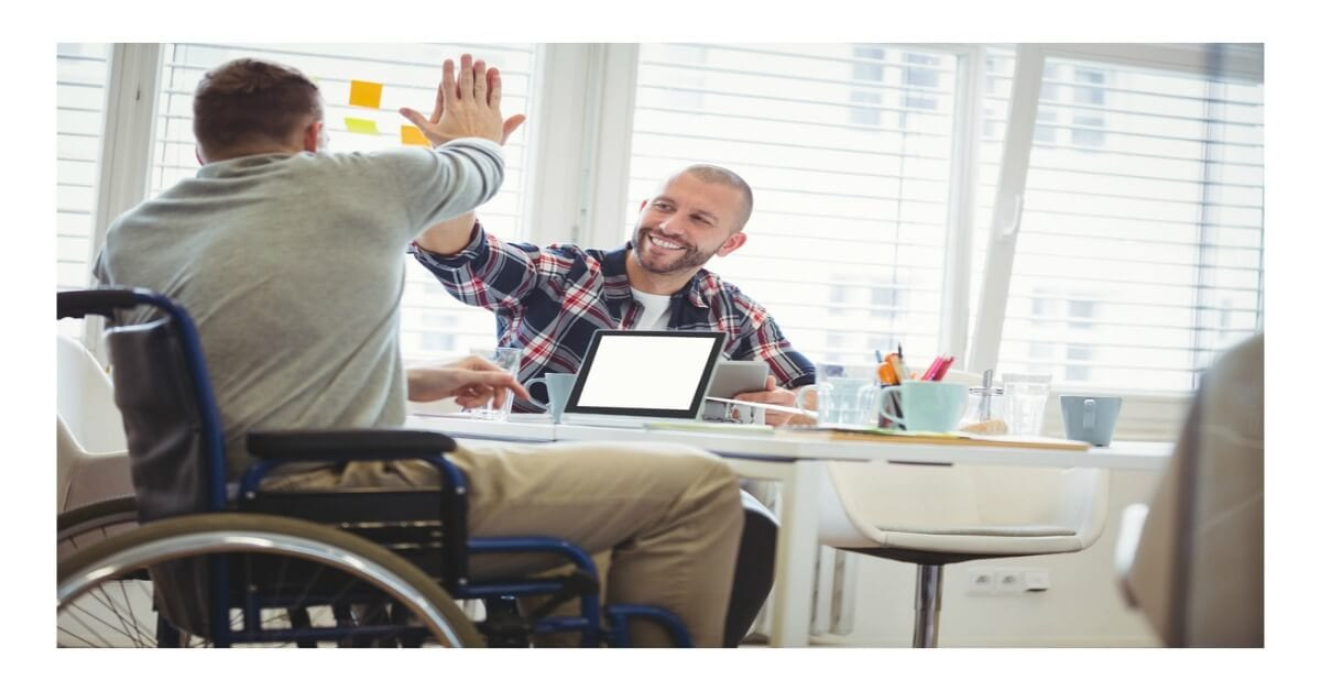 "disability ally - two men are seated, one in a wheelchair and the other on a chair, their hands are raised in a ""high five"" salute"