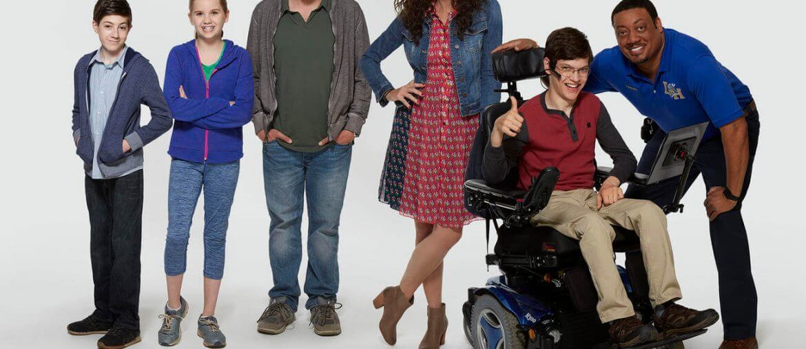 cast of the Speechless TV show stand in line - 2 children, mom, dad, 1 teenager who is a wheelchair user, and the aide (who is a man)