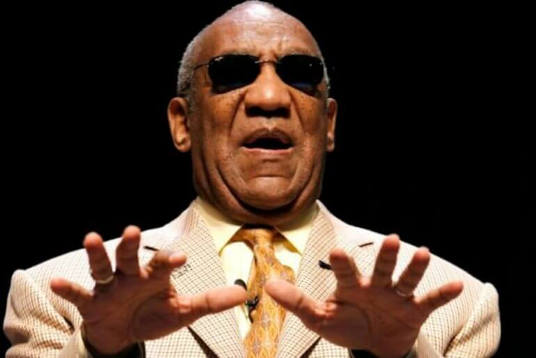 """bill cosby blind - a man with dark brown skin and balding grey hair and black sunglasses is wearing a tan suit with dark orange tie, holding his hands forward as if he is using them to """"see"""""""