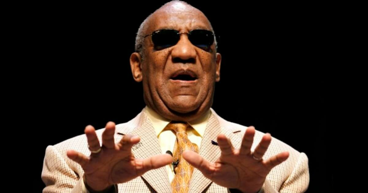 bill cosby blind - a man with dark brown skin and balding grey hair and black sunglasses is wearing a tan suit with dark orange tie, holding his hands forward as if he is using them to