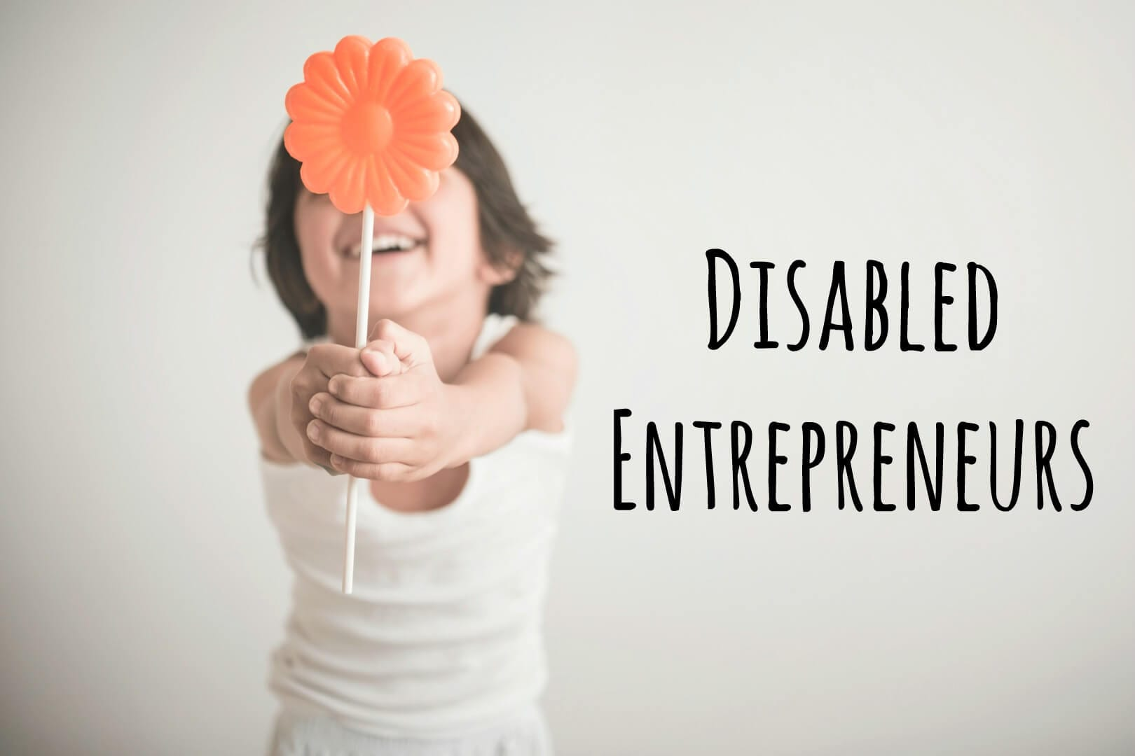 "photo for the gift guide for disability: image description: child holding orange flower in front of her smiiling face. Text to the right reads ""Disabled Entrepreneurs"""