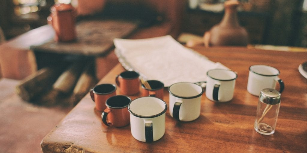 A photo of a table with many mugs on it, as well as papers, indicating people are sitting around it in a casual meeting