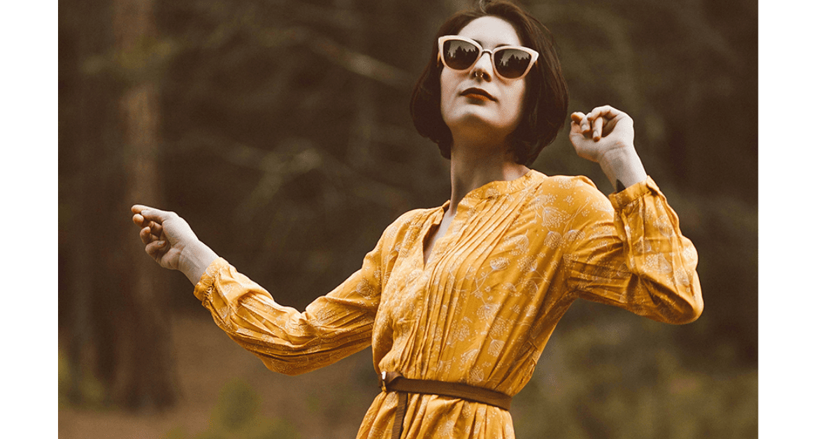 why hire someone with a disability - image of a woman with yellow dress and yellow framed sunglasses looking up. she has a nosing and dark hair and is attractive