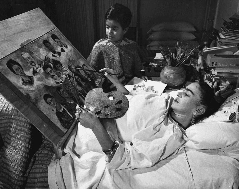 frida kahlo lying in bed and painting