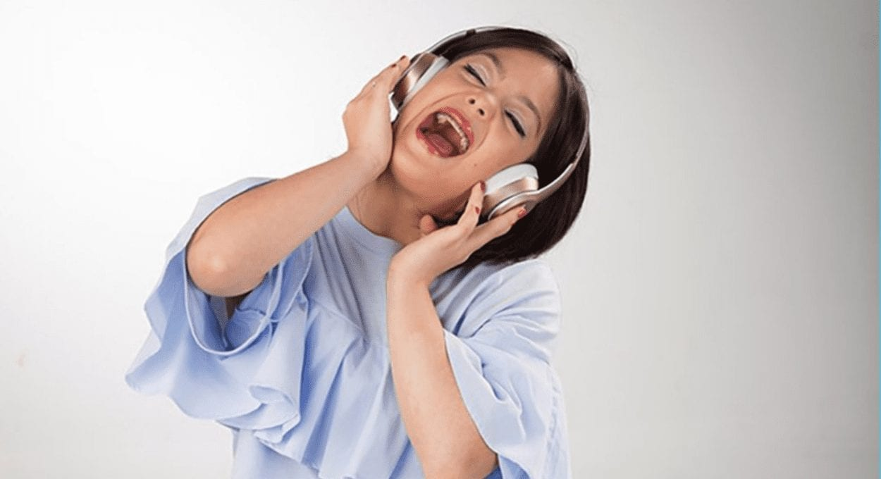 blogger with down syndrome: image description: woman with light blue shirt on and headphones has her head tilted and looks like her mouth is open in song