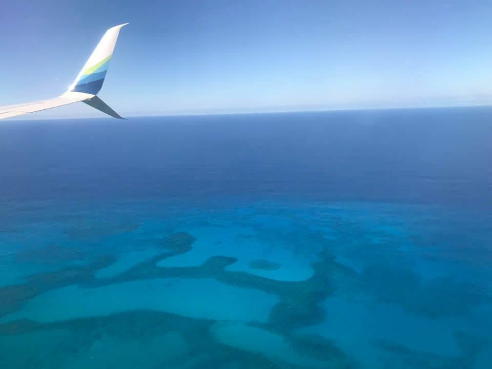 view from airplane of the blue sea below and just glimpsing the airplane tailwing