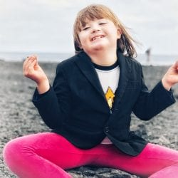 how to get services for your disabled child: photo of a little girl with down syndrome in cross-legged yoga position