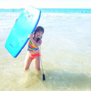 girl with down syndrome holding boogie board: she is standing and smiling on the beach with the water behind her