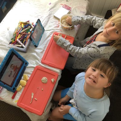 two children, one with down syndrome, with clay and iPads, looking up at the camera, smiling