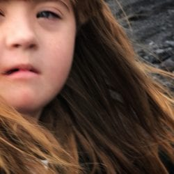 the doctor told me to abort my baby with down syndrome: image of a young girl with down syndrome looking fiercely into the camera, her long brown hair flowing