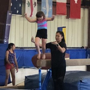 young girl with down syndrome wearing a gymnastics jumper on a high beam, about to jump, there is an adult woman standing by her side making sure she is safe