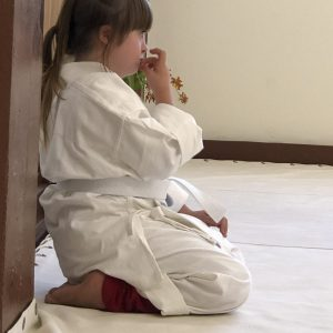 girl with down syndrome in a white martial arts gi sits and waits her turn