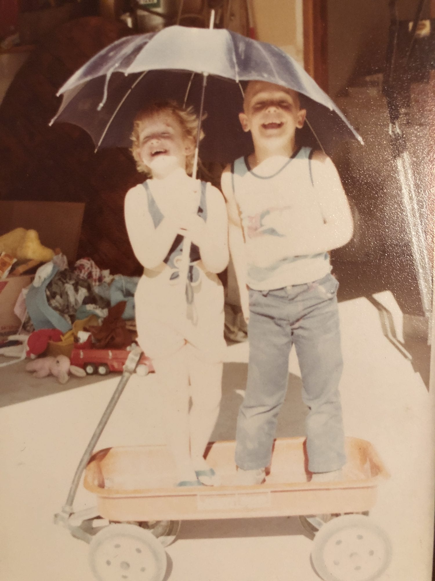 dana and meriah: a boy and a girl playing with an umbrella over them