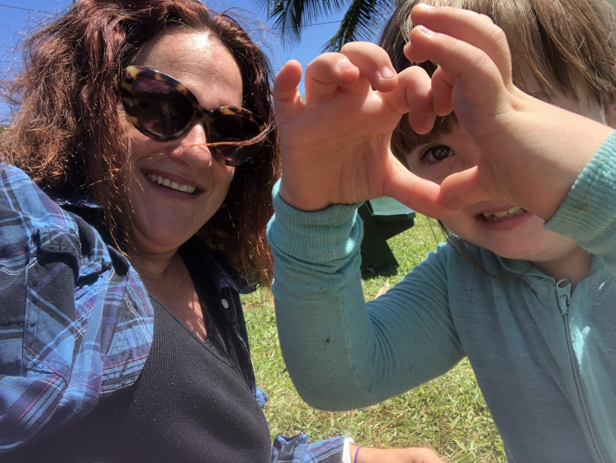 disabled mom parenting project: woman on left with dark hair and sunglasses is smiling while a child is making a heart shape with her hands, also smiling