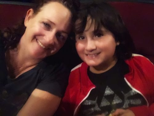 two people facing the camera, smiling: one is a woman, and the other a young boy. they both have dark hair and are smiling