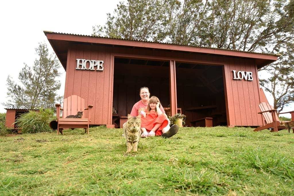 "image description: a woman sits with a girl in front of a a red shed that reads ""hope"" on one side and ""love"" on the other. a cat is walking forward toward the camera"
