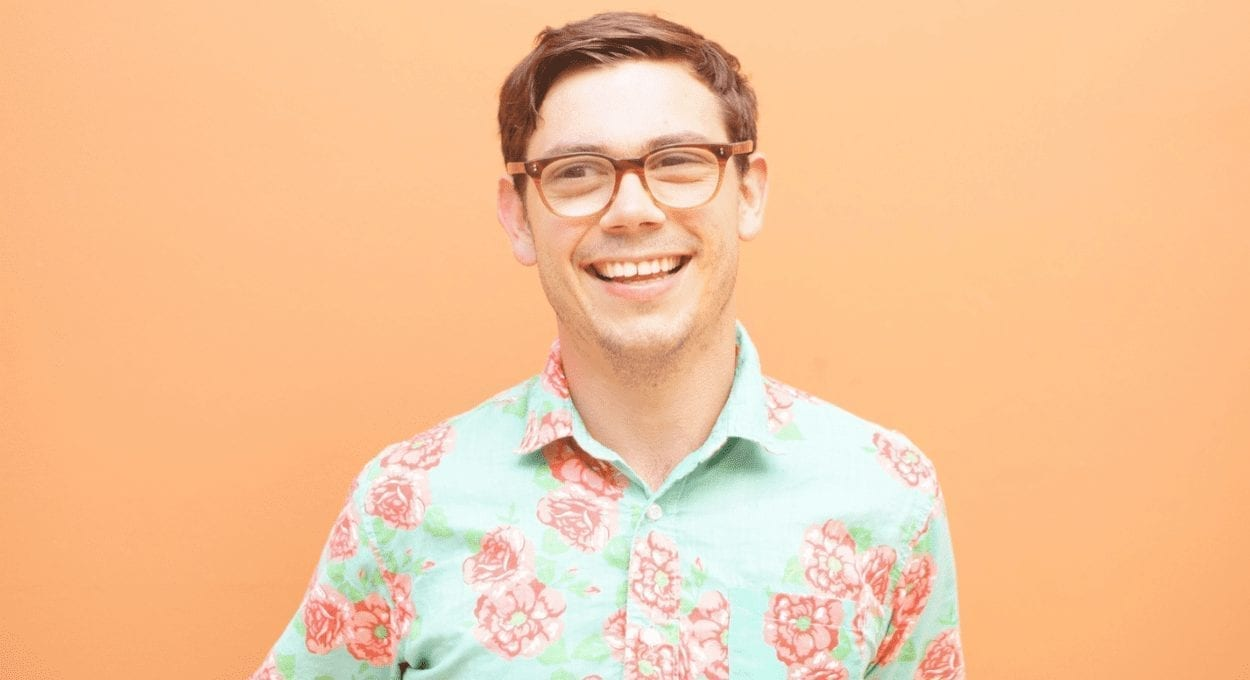 image description of Special Netflix show: light orange background wall with a man with white skin and brown hair wearing glasses smiling at the camera. he is wearing a shirt that is aqua with an orange pattern on it.