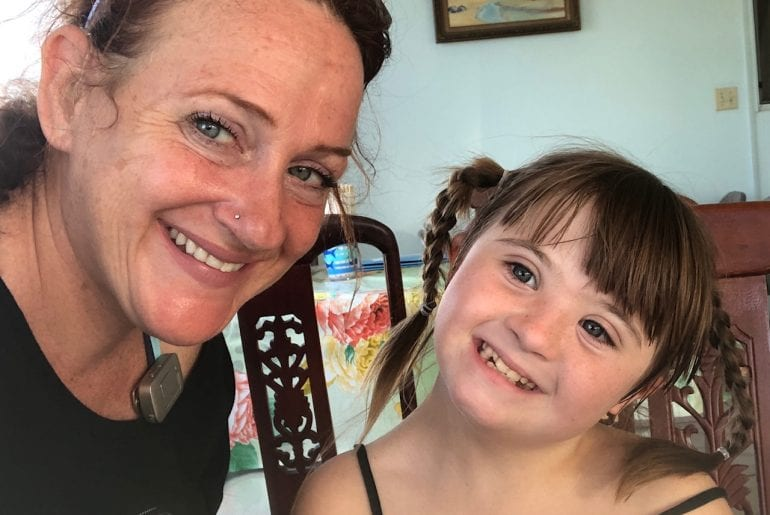 preparing to travel with a disability: image of a woman on the left and a young girl on the right. they are both smiling, with brown hair and light eyes. the woman is wearing hearing aids and the child has Down syndrome