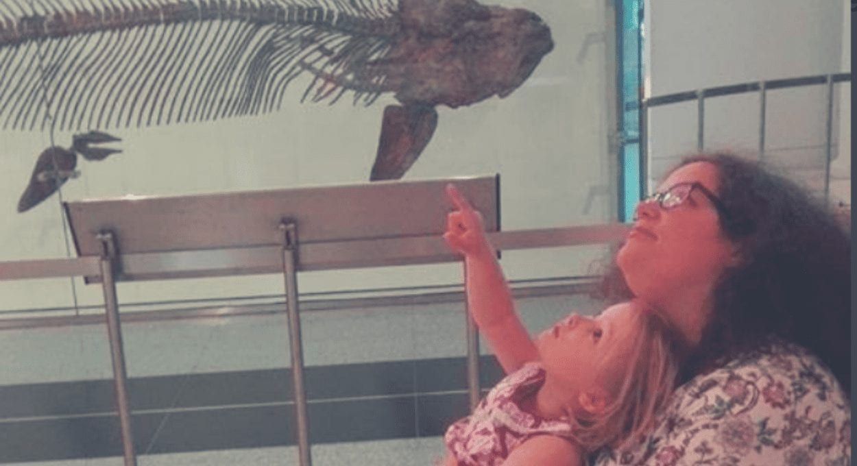 Disabled Moms Interview Project: Featuring Lorna Duff image description: a lithg skinned woman in a wheelchair with a light skinned child on her lap look up at the floating bones of a dinosaur - the child is pointing up