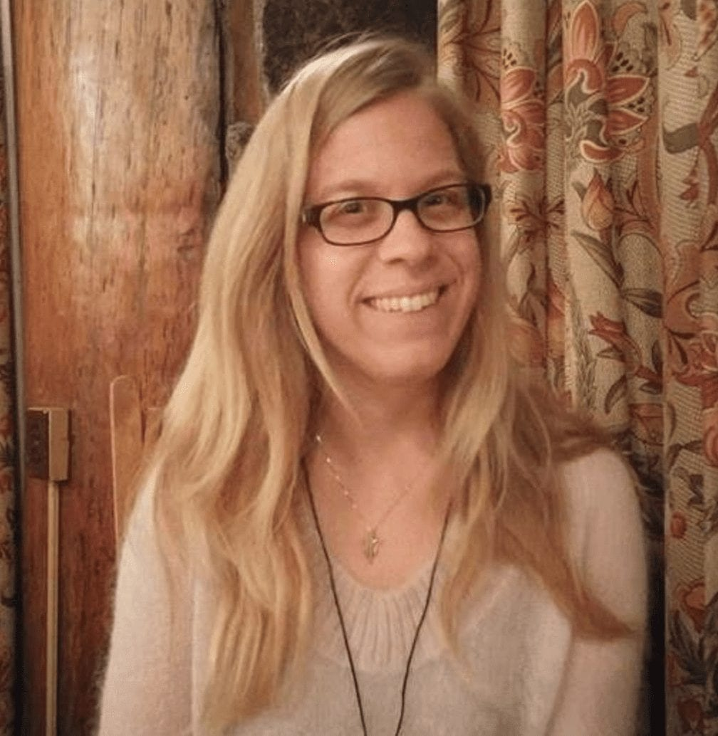 A white woman with long blond hair and glasses sits in front of red and green brocade curtains, beaming into the camera. She's wearing a fluffy pink sweater and two necklaces, one on a short gold chain and the other on a long black leather cord