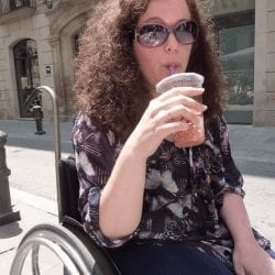 Lorna Duff Howie a woman with light skin and curly auburn hair sits in a wheelchair and sips form a glass from a straw. she is wearing sunglasses