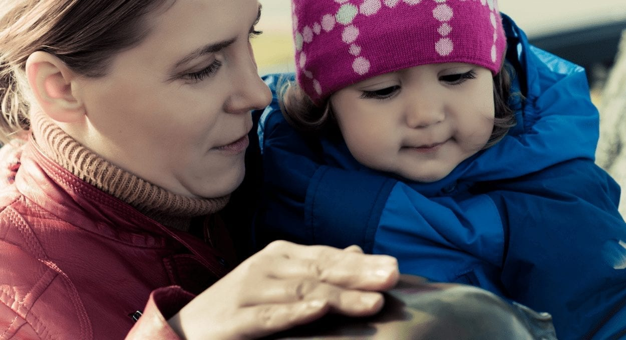 disabled mom parenting project: image description: woman holding a child, the woman is signing. they are light skinned and wearing warm clothing