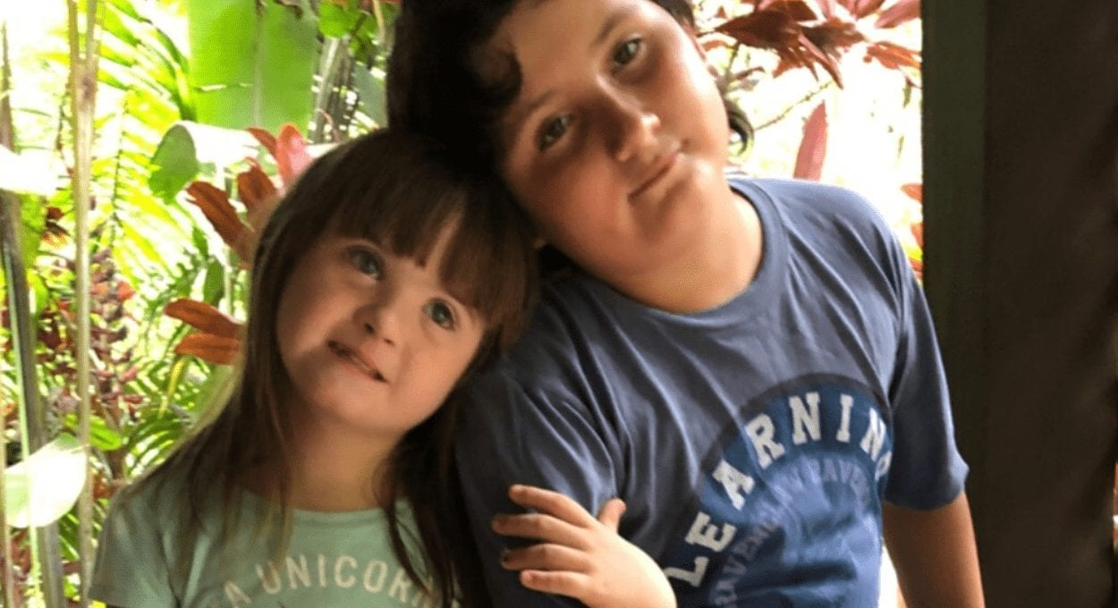 the power and value of the neurodiverse: image of a girl and a boy, the girl has down syndrome and the boy has asperger's. they are sitting with their heads leaning on each other, the girl's hand is wrapped around the boy's arm