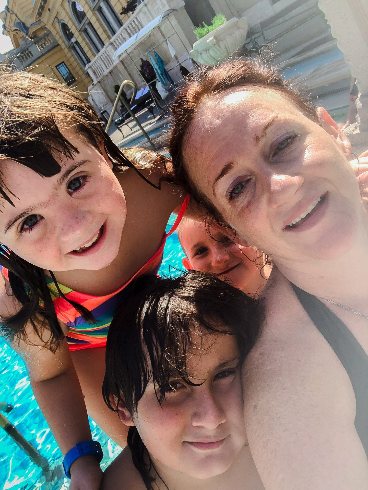 travel with invisible disability in budapest: image of 3 children with brown hair looking at camera and smiling and a woman with invisible disability also smiling; there is water behind them; they are at the szechenyi bath in budapest