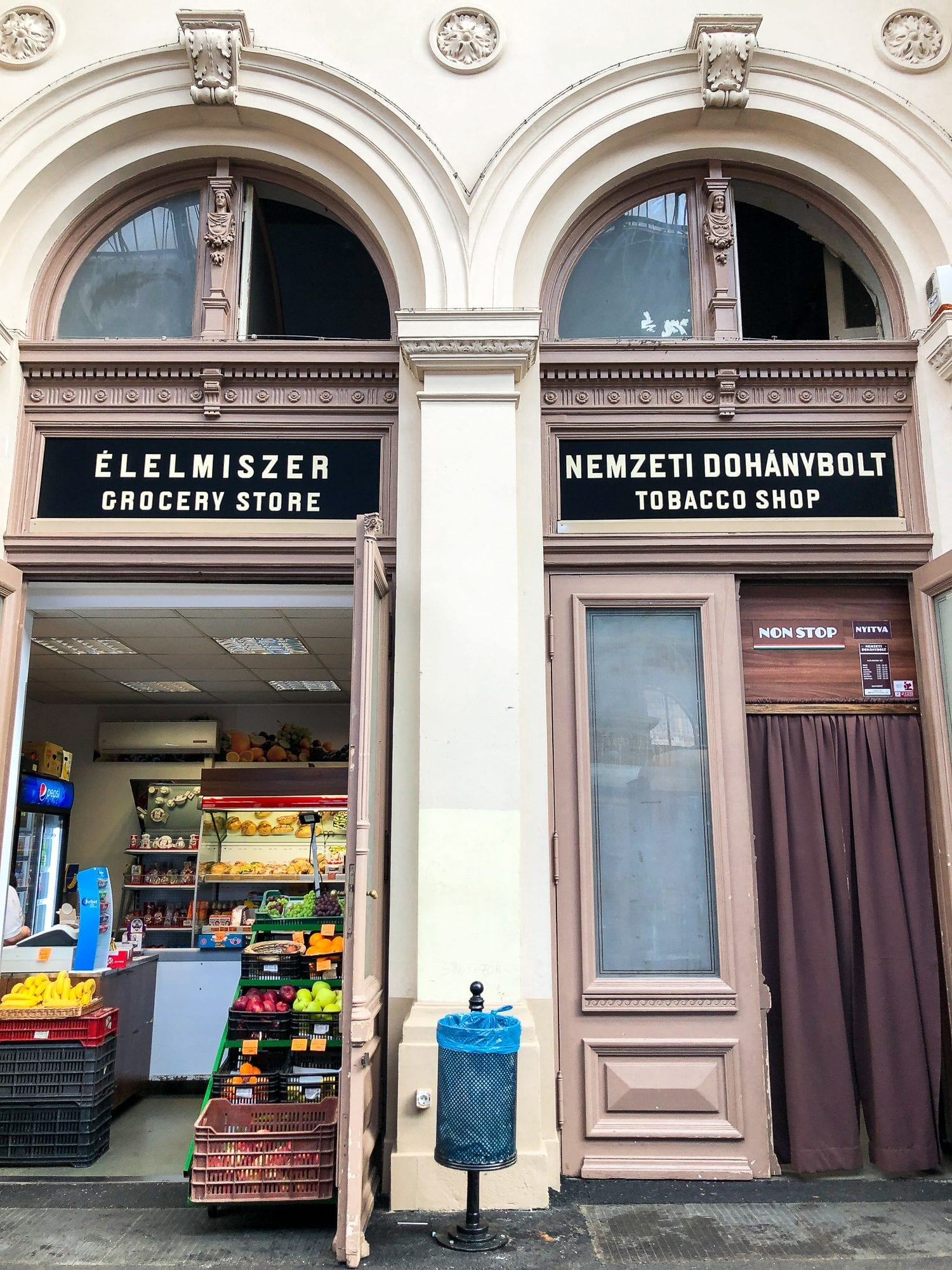 "in kaleti budapest train station, two shops next to each other, one reading grocery store"" and the other reading ""tobbaco shop"""