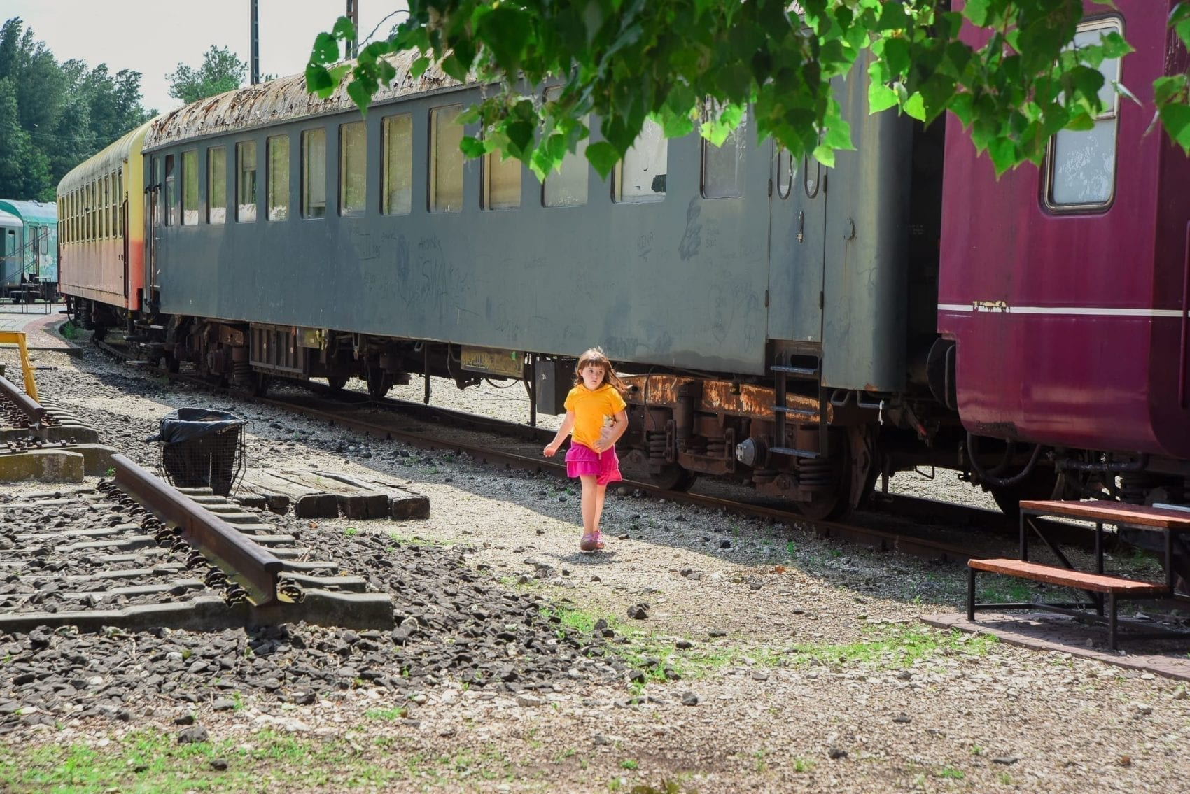 little girl running by trains