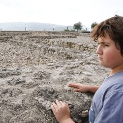 travel with an invisible disability: boy looks out over a castle ruins