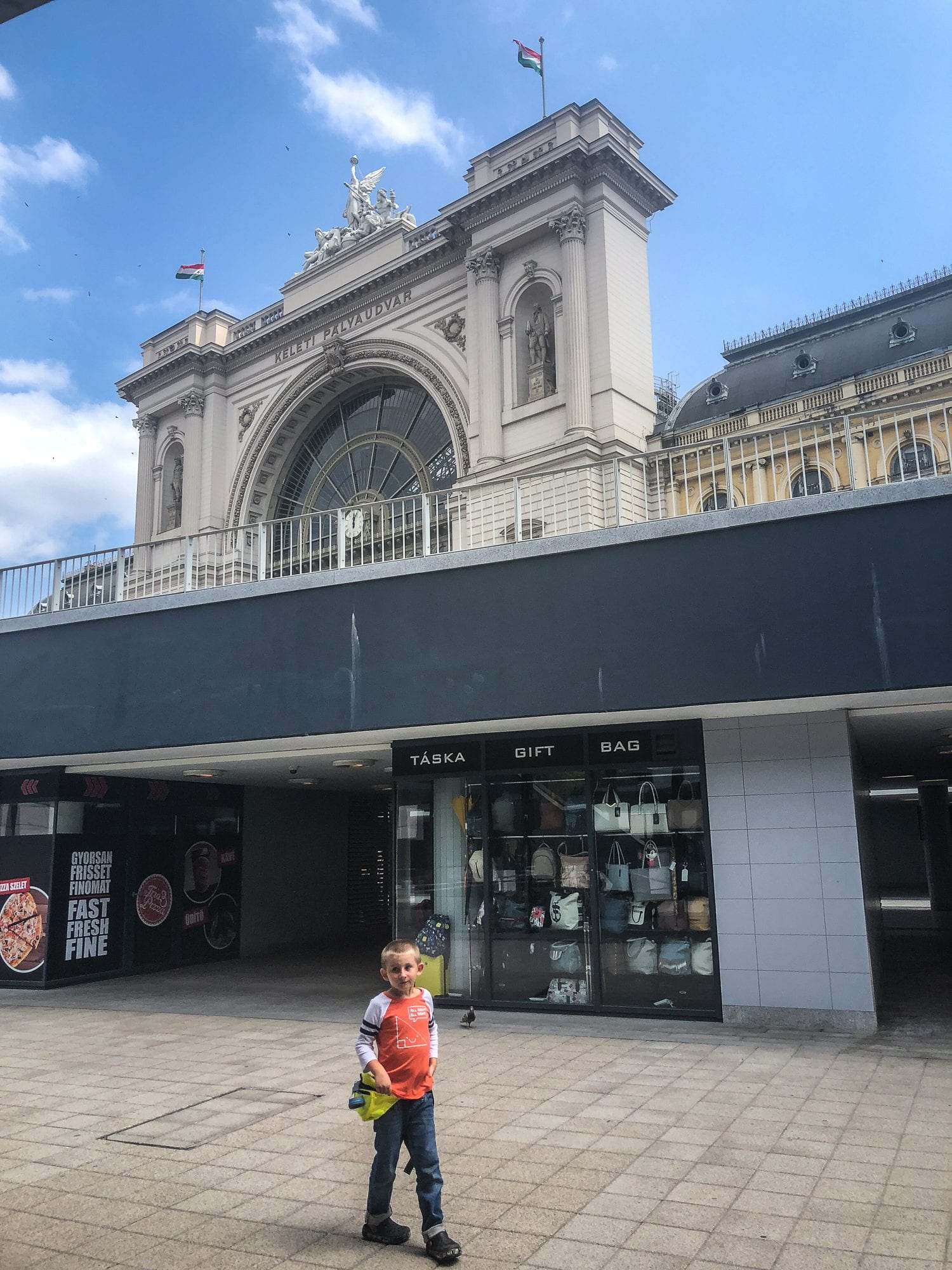 invisible disability in budapest: a boy with an orange shirt in front of the train station