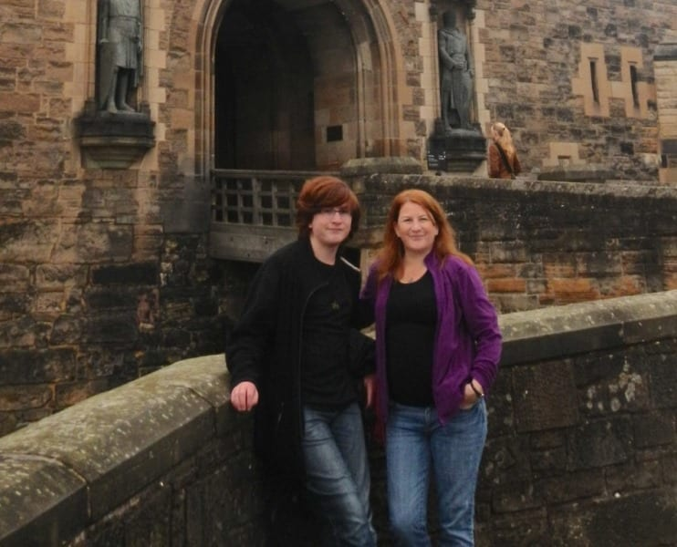 sandi parsons and son: a young man and a woman stand next to each other, the woman has her hand in her jeans pocket and is wearing a purple jacket. the man is wearing black, a castle is in the background. both have dark hair and light skin and are smiling