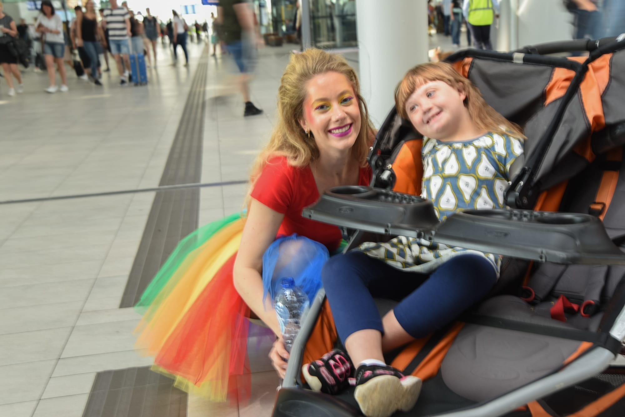 lady in rainbow dress next to a child in a stroller. both are smiling