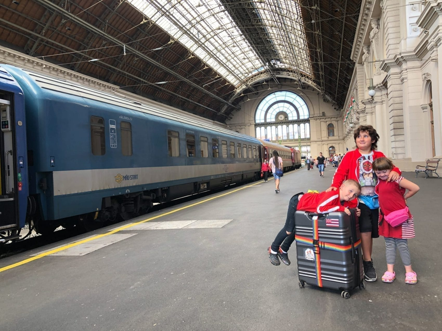 on the night train to budapest - the european sleeper train with children - image description: three children stand in the budapest train station with a train in the background and luggage around them