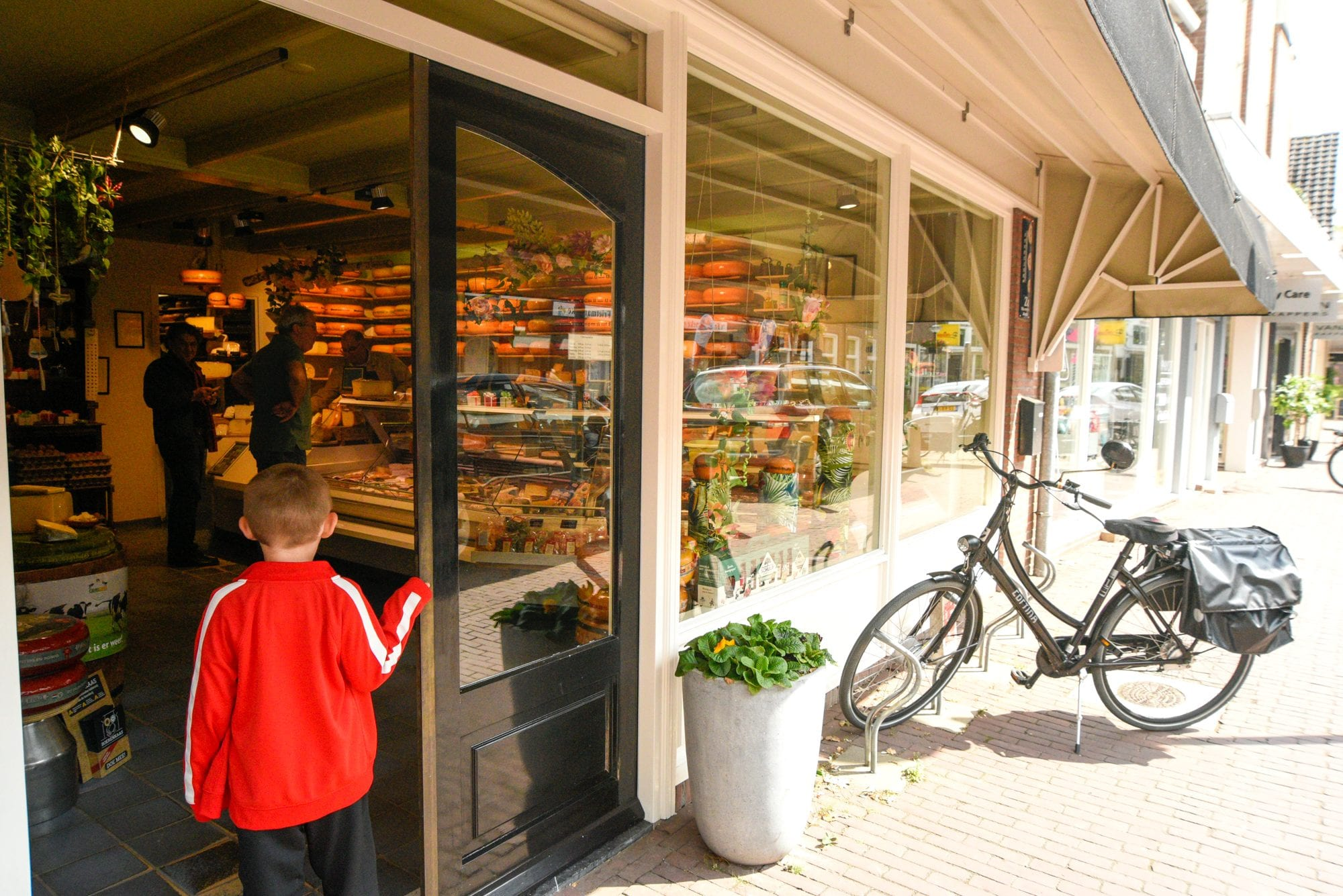 cheese shop with a small boy in red jacket at door. a bicycle is parked outside