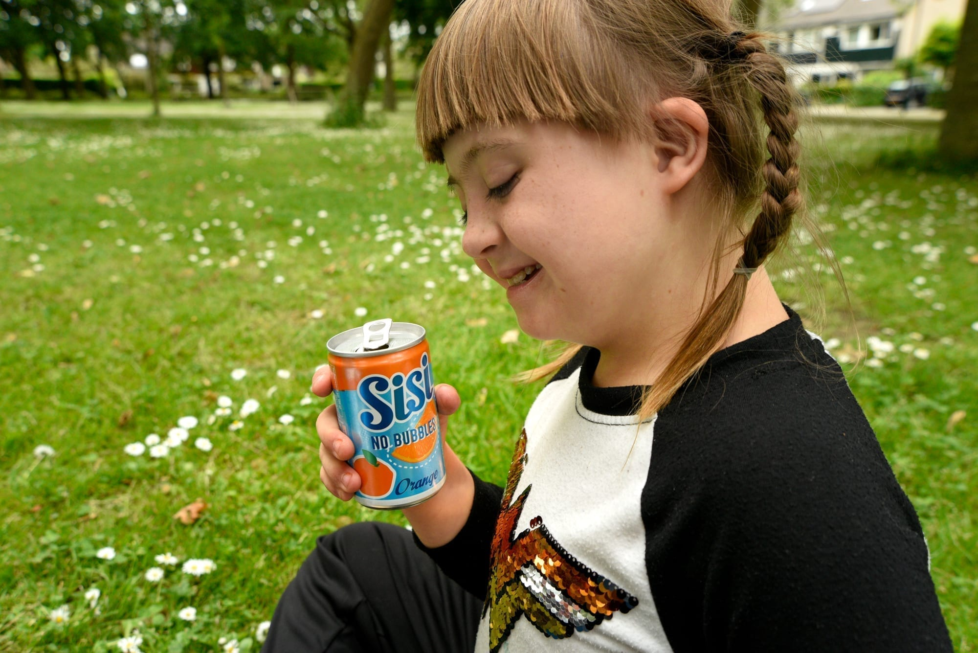 moxie in a park with a can of orange juice
