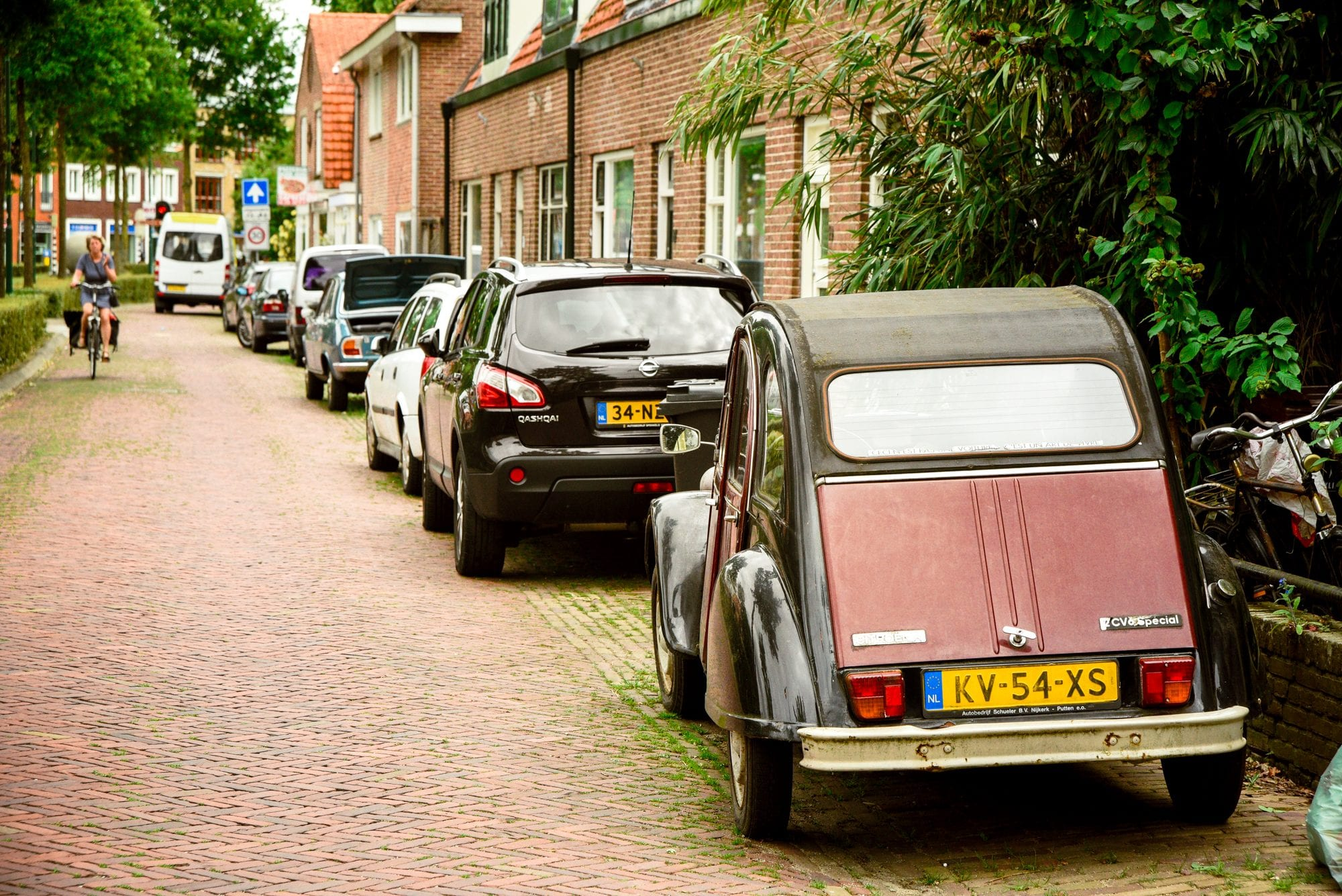 cars on the side of the road, with an old model citroen closest, the road is cobblestone