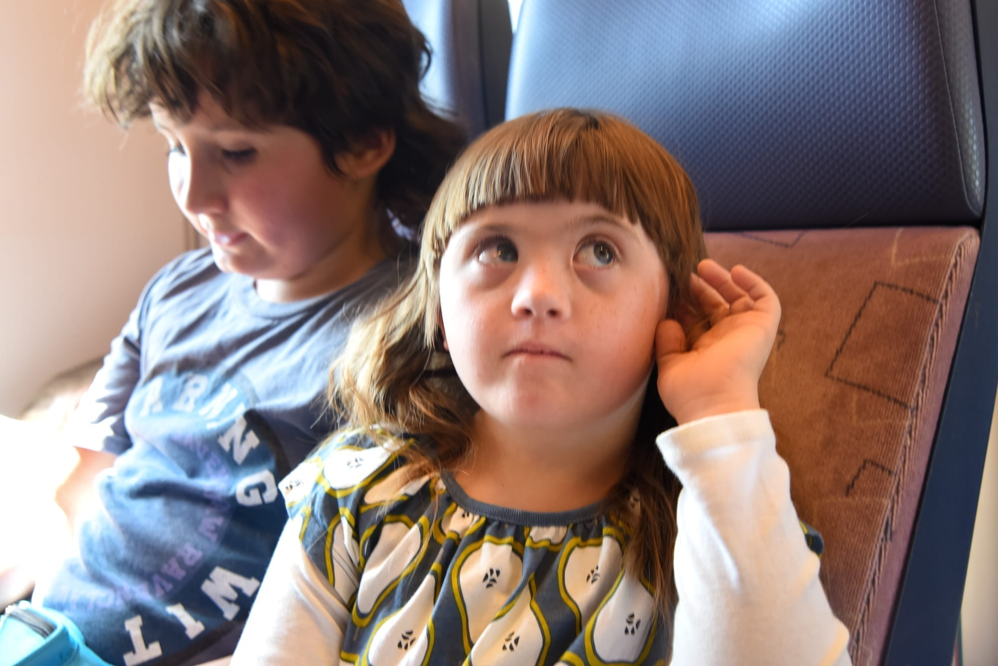 access on trains in holland: a little girl cups her ear and is listening